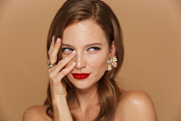 Zbliżenie na piękną młodą kobietę noszenie akcesoriów do makijażu i biżuterii pozowanie na białym tle nad beżową ścianą, trzymając rękę na jej twarzy