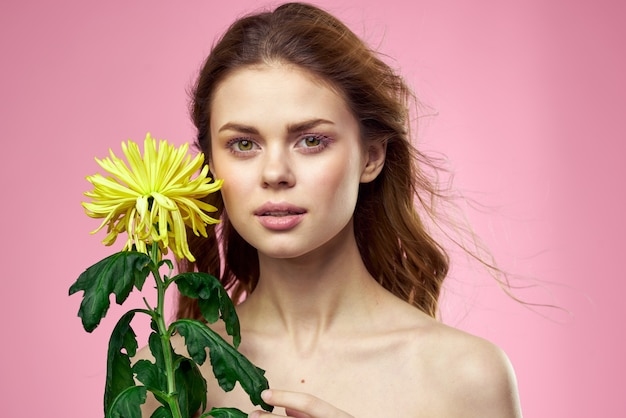 Zbliżenie na piękną młodą kobietę z kwiatem