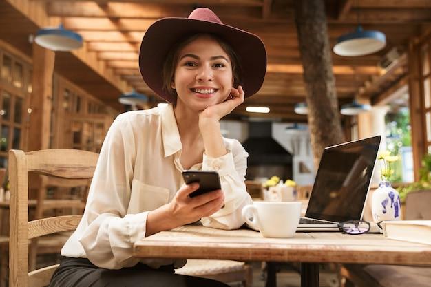 Zbliżenie na piękne kobiety w kapeluszu siedzi przy stoliku kawiarnianym