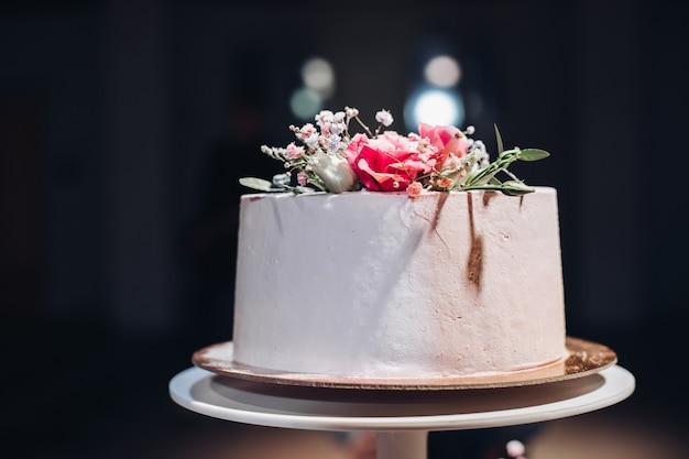 Zbliżenie na piękny biały gładki tort weselny ozdobiony suszonymi kwiatami na górze w sztucznym świetle.
