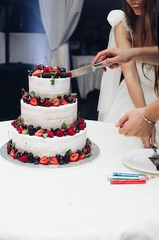 Zbliżenie na piękny tort weselny z białym serem ozdobionym pysznymi świeżymi jagodami na każdej warstwie. ozdobiona truskawkami, jagodami, wiśniami i jeżynami.