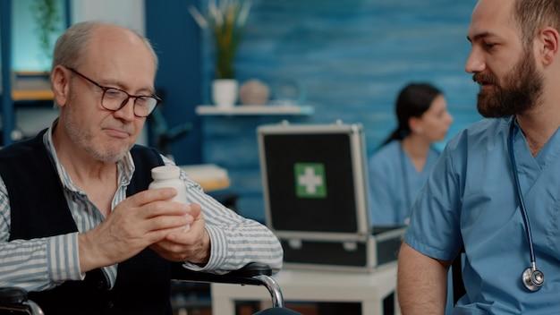 Zbliżenie na pielęgniarkę trzymającą butelkę tabletek do leczenia niepełnosprawnego pacjenta