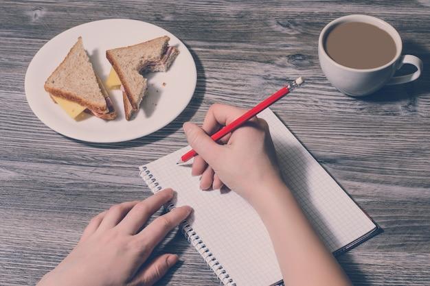 Zbliżenie na pisanie ręki w notatniku i smaczne kanapki z serem na okrągłym talerzu, filiżanka latte. drewniane tło, widok z góry