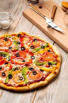 Zbliżenie na pizzę warzywną z oliwkami i pieprzem