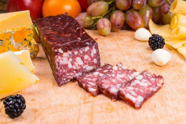 Zbliżenie na plasterki wędlin na desce serów dla smakoszy z różnymi serami i przyozdobionymi owocami