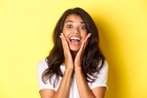 Zbliżenie na podekscytowaną, piękną afroamerykańską dziewczynę, z otwartymi ustami i patrzącą zdumioną na coś fajnego, oglądającą reklamę, stojącą na żółtym tle.