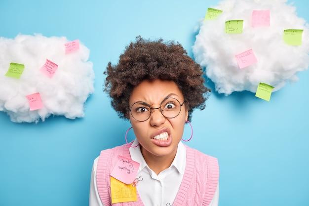 Zbliżenie na podrażnioną, kręconą, młodą pracownicę biurową z kręconymi włosami zaciska zęby, wygląda na zirytowaną, ma termin i wiele zadań zapisuje informacje do zapamiętania na naklejkach z notatkami