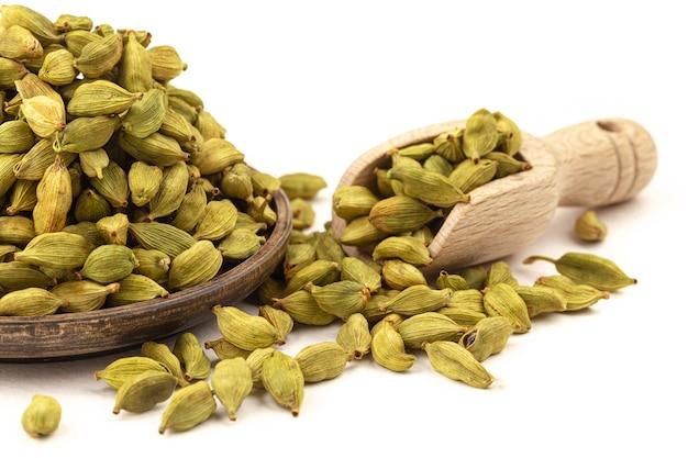 Zbliżenie na pojedyncze nasiona kardamonu w drewnianej tablicy i na białym tle miarka
