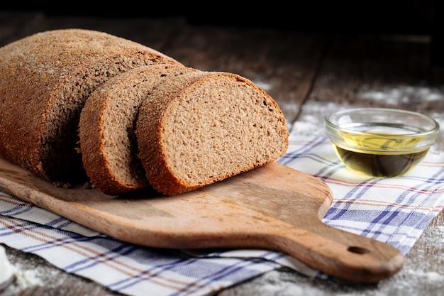 Zbliżenie na pokrojony szary bochenek chleba z olejem