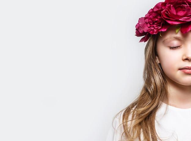 Zbliżenie na pół twarzy małej dziewczynki z zamkniętymi oczami i kwiatami na głowie na jasnym tle