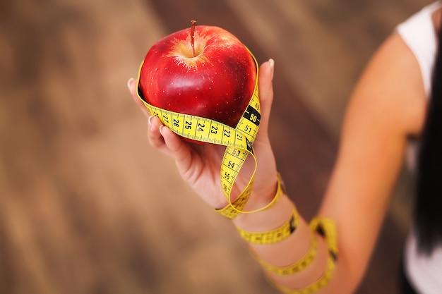 Zbliżenie na pomiar jabłka w rękach kaukaski womans