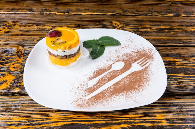 Zbliżenie na poszczególne dekadencki deser ciasto owocowe podawane na białym talerzu z ozdobą z liści mięty i konturami naczyń posypane kakao na powierzchni drewnianego stołu