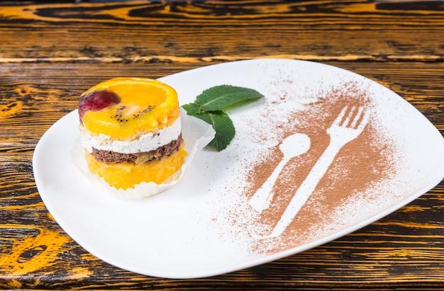 Zbliżenie na poszczególne dekadencki deser ciasto owocowe podawane na białym talerzu z ozdobą z liści mięty i konturami naczynia posypane kakao na powierzchni drewnianego stołu