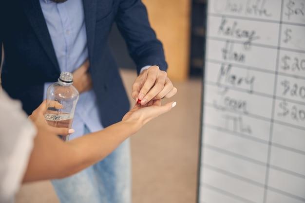 Zbliżenie na pracownika płci męskiej przyjmującego leki od kobiety podczas bólu brzucha w pracy