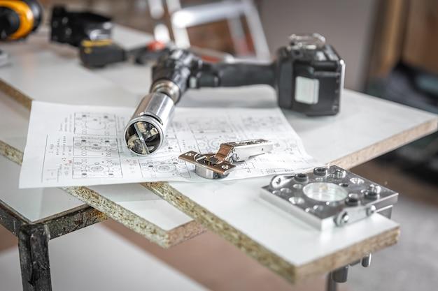 Zbliżenie na precyzyjny uchwyt do wiercenia i inne narzędzia stolarskie.