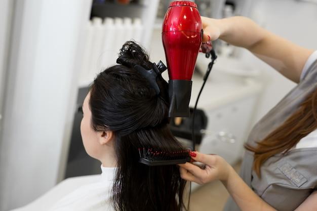 Zbliżenie na proces stylizacji włosów w gabinecie kosmetycznym z suszarką i grzebieniem. fryzjer suszy dziewczyny mokre włosy suszarką do włosów i czesze grzebień