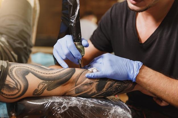 Zbliżenie na profesjonalnego tatuatora wykonującego tatuaż na ramieniu młodego mężczyzny maszyną z czarnym atramentem