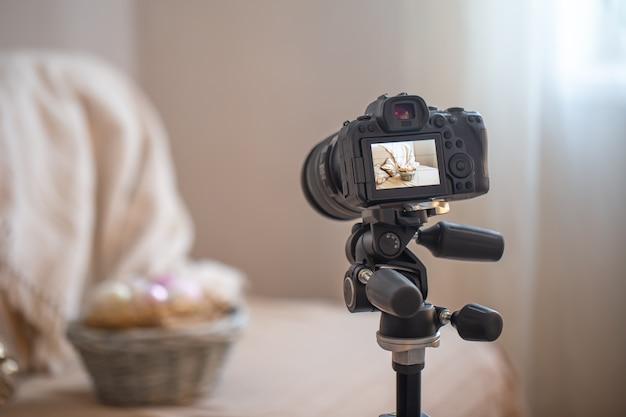 Zbliżenie na profesjonalny aparat cyfrowy na statywie podczas fotografowania domowej kompozycji na rozmytym tle