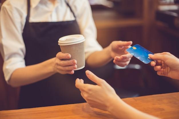 Zbliżenie na profesjonalny barista. kobieta daje filiżankę kawy i bierze kartę kredytową