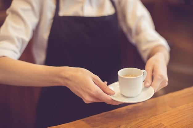 Zbliżenie na profesjonalny barista. kobieta robi kawę i ją prezentuje