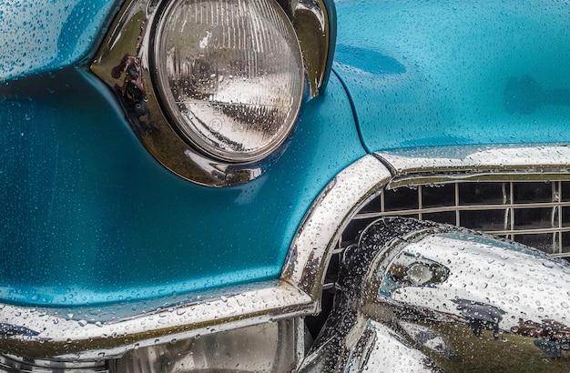 Zbliżenie na przednią część niebieskiego samochodu, w tym światła i zderzak