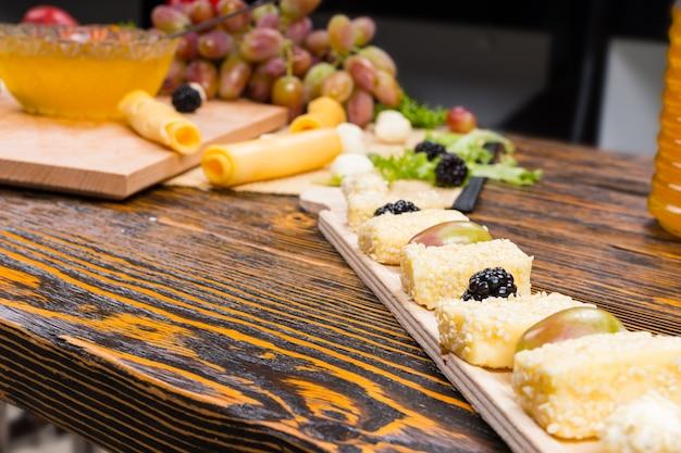 Zbliżenie na przekąskę z owocami i serami dla smakoszy na rustykalnym drewnianym stole z miejscem na kopię