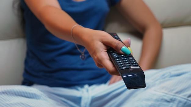 Zbliżenie na przełączanie programów telewizyjnych siedząc na kanapie za pomocą pilota. ujęcie kontrolera w rękach osoby wskazującej na telewizor, naciskającej przycisk i zmieniającej kanały siedzącej przed telewizorem