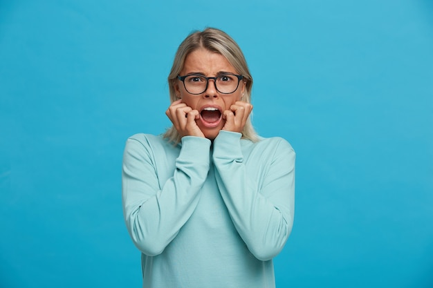Zbliżenie na przestraszoną blondynkę, wygląda na przestraszoną, przestraszoną, usta szeroko otwarte, jak krzyczą głośno,