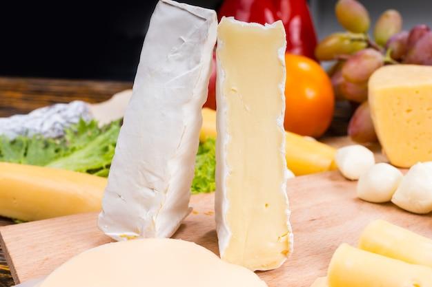 Zbliżenie na przystawkę dla smakoszy deska serowa z klinami sera brie stojąca pionowo na drewnianej desce i otoczona świeżymi owocami