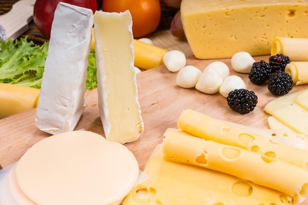 Zbliżenie na przystawkę z serami dla smakoszy z serami brie, szwajcarskimi i provolone przyozdobionymi jagodami