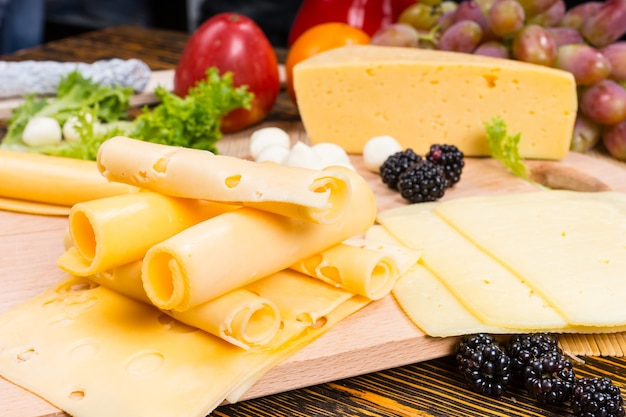 Zbliżenie na przystawkę z serami dla smakoszy z walcowanymi plastrami sera szwajcarskiego i przyozdobionymi świeżymi owocami
