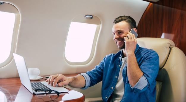 Zbliżenie na przystojnego mężczyznę w swobodnym stroju, który uśmiecha się, pisze coś na laptopie i trzyma smartfon w lewej ręce, lecąc pierwszą klasą samolotu.