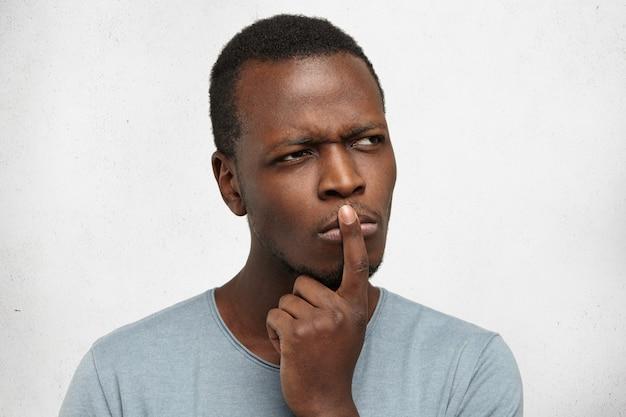 Zbliżenie na przystojnego młodego czarnoskórego mężczyznę o skoncentrowanym zamyśleniu, zmarszczonym brwi, trzymającym palec na ustach, jakby chciał coś sobie przypomnieć lub mówiąc: a co jeśli…