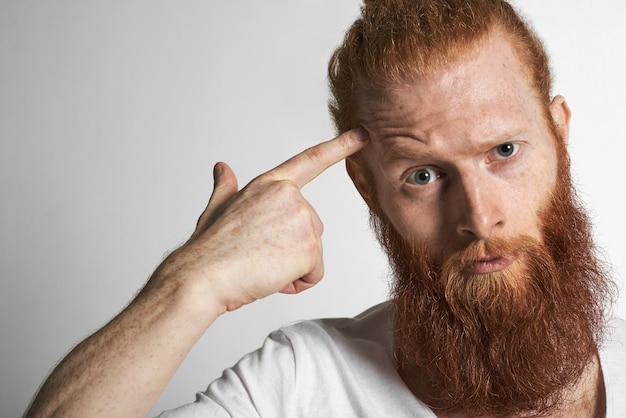 Zbliżenie na przystojnego, młodego europejczyka, rudowłosego mężczyzny z piegami i rozmytą brodą, marszczącego brwi, wpatrującego się w kamerę ze złością lub oburzeniem, jakby mówił: czy zwariowałeś. wyraz twarzy człowieka