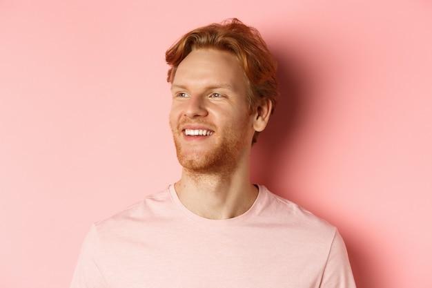 Zbliżenie na przystojnego młodego mężczyznę z brodą i rudymi włosami, patrzącego w lewo i uśmiechniętego zachwyconego, stojącego pewnie na różowym tle