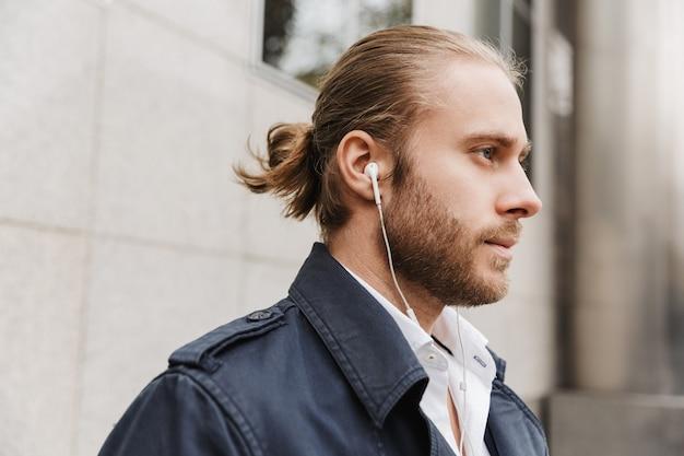 Zbliżenie na przystojnego, pewnego siebie, młodego, brodatego biznesmena stojącego na zewnątrz na ulicy, słuchającego muzyki przez słuchawki