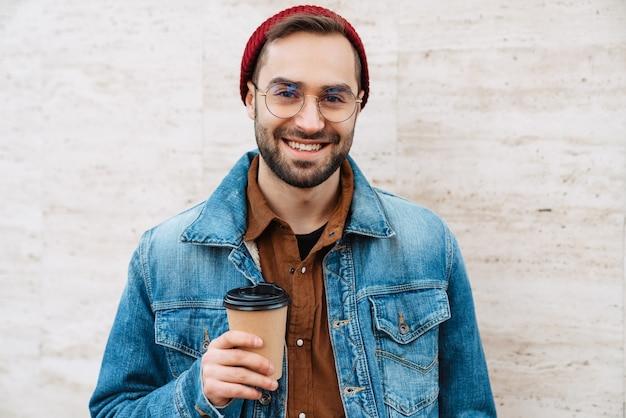 Zbliżenie na przystojnego, szczęśliwego młodego, stylowego brodatego mężczyznę spacerującego na świeżym powietrzu po ulicy, trzymającego filiżankę kawy na wynos
