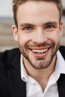 Zbliżenie na przystojnego uśmiechniętego młodego biznesmena nad murami miasta