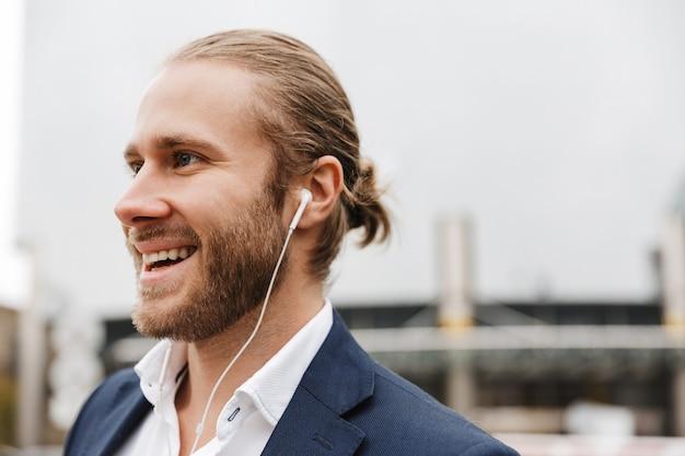 Zbliżenie na przystojnego uśmiechniętego młodego brodatego biznesmena stojącego na zewnątrz na ulicy, słuchającego muzyki przez słuchawki