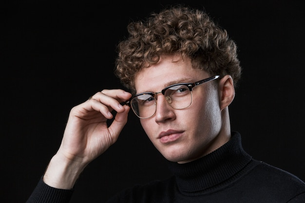 Zbliżenie na przystojny, pewny siebie młody biznesmen z kręconymi włosami, ubrany w golf, stojący przed odosobnioną czarną ścianą, pozowanie w okularach