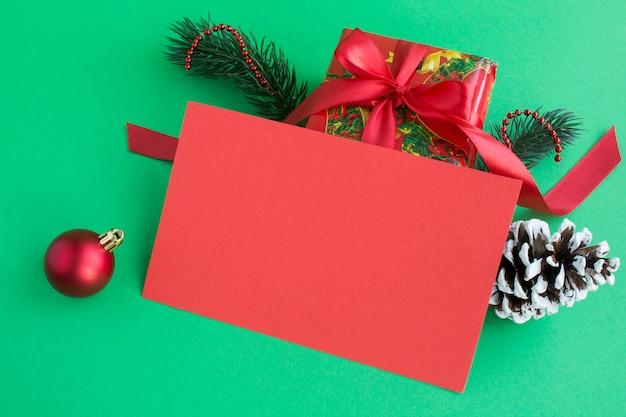 Zbliżenie na pustym czerwonym papierze na życzenia świąteczne i prezent na zielonym tle