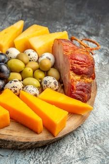 Zbliżenie na pyszną przekąskę, w tym owoce i żywność na brązowej tacy na lodowym tle