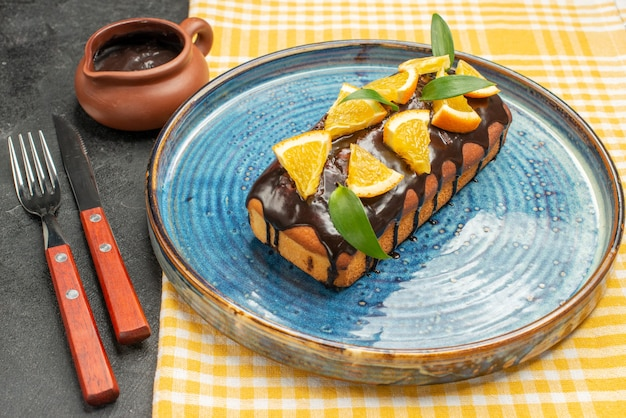 Zbliżenie na pyszne ciasto ozdobione pomarańczą i czekoladą podawane z widelcem i nożem