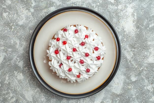 Zbliżenie na pyszne kremowe ciasto ozdobione owocami na lodowym tle