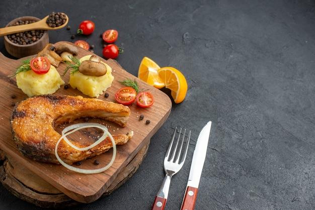 Zbliżenie na pyszne smażone ryby i pomidory z grzybami na desce do krojenia sztućce ustawiają pieprz na czarnej powierzchni
