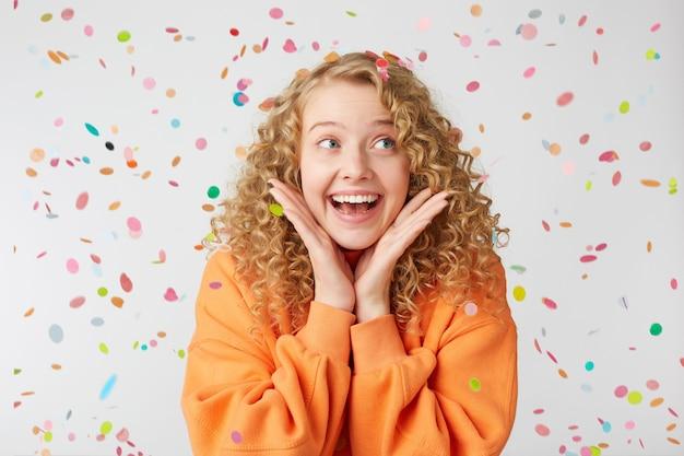 Zbliżenie na radośnie uśmiechniętą śliczną, delikatną, ładną blondynkę, która wygląda na prawą stronę, jest podekscytowana, zaskoczona, trzyma dłonie blisko twarzy, ubrana w duży pomarańczowy sweter, stoi pod spadającym konfetti