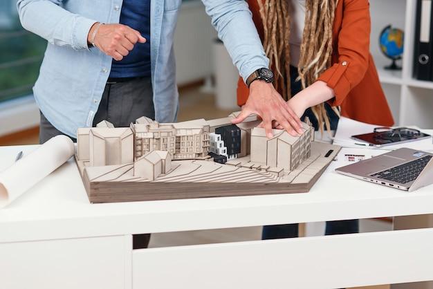 Zbliżenie na ręce architektów płci męskiej i żeńskiej analizujących projekt przyszłego kompleksu mieszkalnego.
