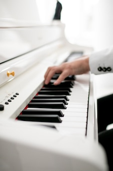 Zbliżenie na ręce człowieka na pianinie grający męskie ręce pianisty na klawiaturze fortepianu