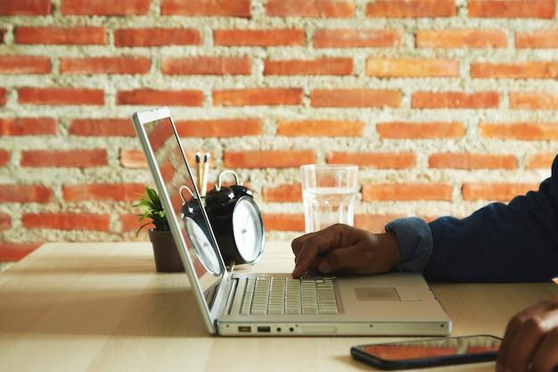 Zbliżenie na ręce człowieka pisania na klawiaturze laptopa na stole z promieniami słonecznymi