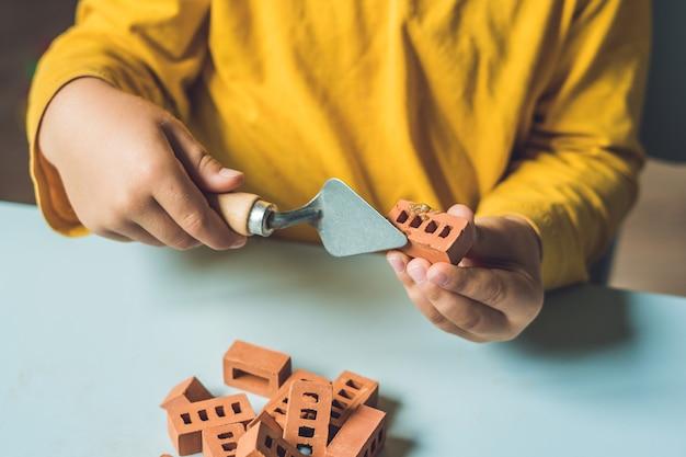 Zbliżenie na ręce dziecka, grając z prawdziwych małych glinianych cegieł przy stole